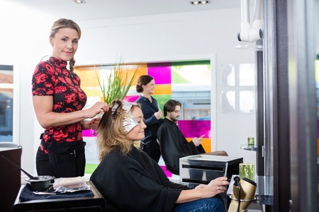 beauty parlor: Portrait of mid adult hairdresser highlighting customers hair in beauty parlor