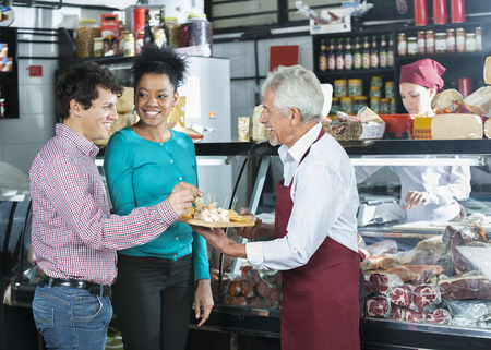 samples: Happy salesman offering free samples to customers in cheese shop