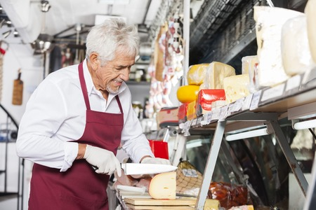 slicing: Happy senior salesman slicing cheese at counter in shop