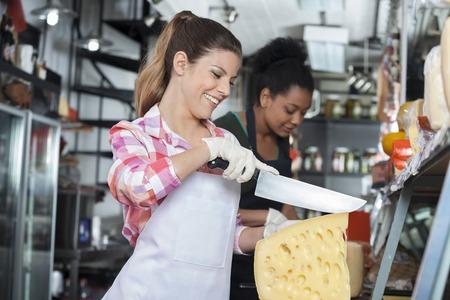 mandil: mujer joven feliz cortando el queso en el mostrador con su colega de trabajo en segundo plano
