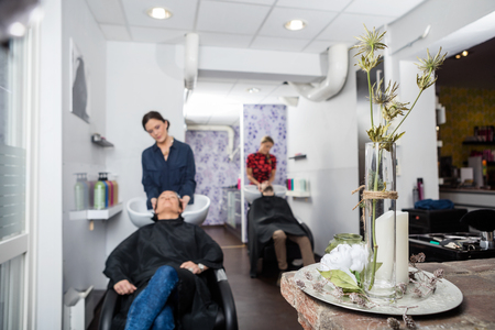 parlour: Flower vase on table in salon with hairdressers washing customers hair in background Stock Photo