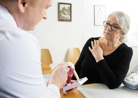 Senior woman looking at male doctor explaining shoulder rotator cuff model in clinic Stock Photo