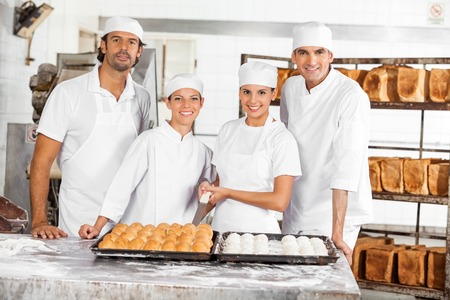 pastry shop: Portrait of confident Bakers with breads standing at table in bakery