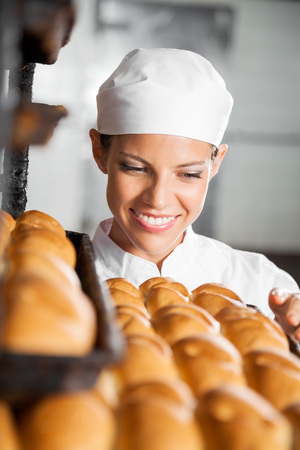 panino: Beautiful female baker looking at fresh breads in bakery