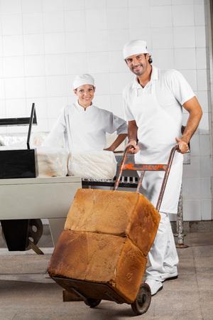 carretilla de mano: Retrato de los trabajadores masculinos confianza empujando barras de pan en la carretilla de mano, mientras que un compañero de trabajo que sonríe en la panadería Foto de archivo