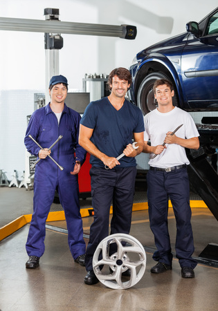 hubcap: Portrait of happy male mechanics holding worktools while standing at garage Stock Photo