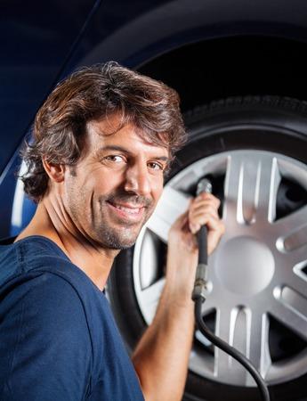refilling: side view portrait of male mechanic refilling car tire at auto repair shop