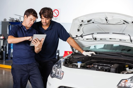 Male mechanics using tablet computer by car with open hood at auto repair shop