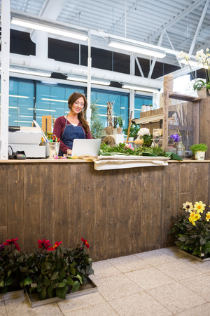 mid adult   female: Happy mid adult female florist using laptop at counter in flower shop