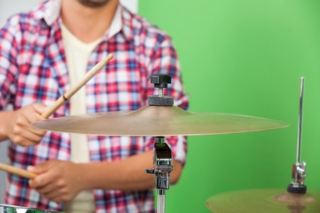 midsection: Midsection of male professional playing cymbal in recording studio