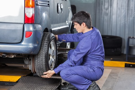 replacing: Side view of male mechanic replacing car tire at auto repair shop Stock Photo