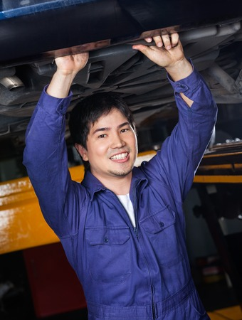 underneath: Portrait of confident male mechanic working underneath car at auto repair shop Stock Photo