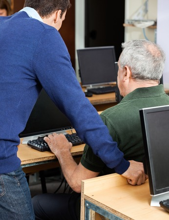 the elderly tutor: Side view of young teacher assisting senior man at computer desk in classroom Stock Photo