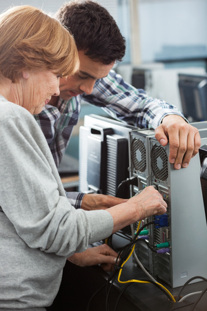 the elderly tutor: Male tutor and senior woman fixing computer in classroom Stock Photo