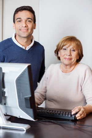 the elderly tutor: Portrait of happy tutor and senior woman at desk in computer lab