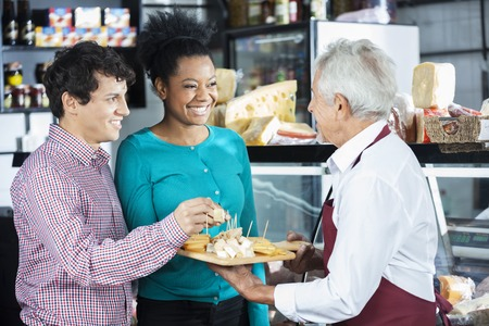Happy salesman offering free cheese samples to customers in shop