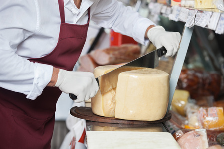 handled: Midsection of salesman slicing cheese with double handled knife at counter Stock Photo
