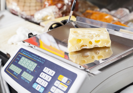 produces: Packed cheese on weight scale in grocery store Stock Photo