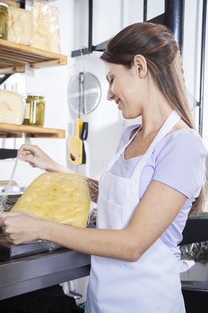 saleswoman: Smiling young saleswoman packing cheese at grocery store