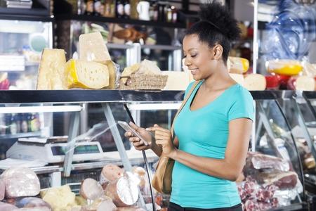 supermercado: mujer joven que usa el teléfono celular en la tienda de comestibles que sonreían