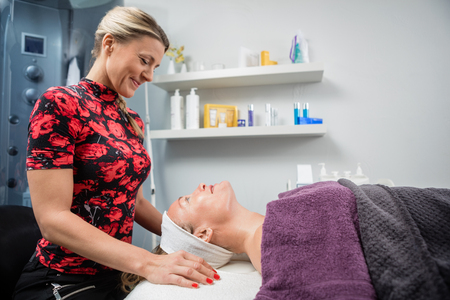 beautician: Side view of beautician smiling while looking at customer undergoing beauty treatment in salon