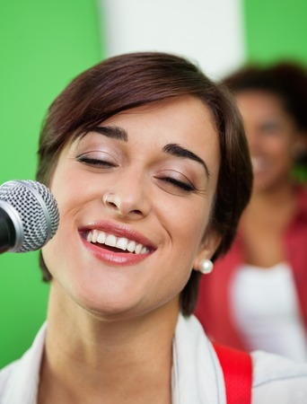 eyes closing: Beautiful woman singing while closing eyes in recording studio
