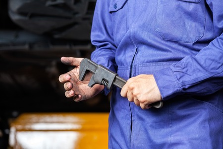 adjustable wrench: Midsection of mechanic holding metallic adjustable wrench in garage Stock Photo
