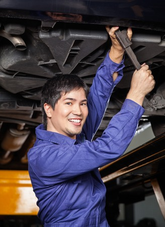 underneath: Portrait of happy male mechanic working underneath lifted car at auto repair shop