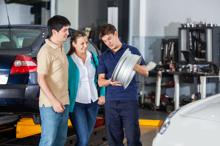 hubcap: Male technician explaining metallic hubcap to couple at garage