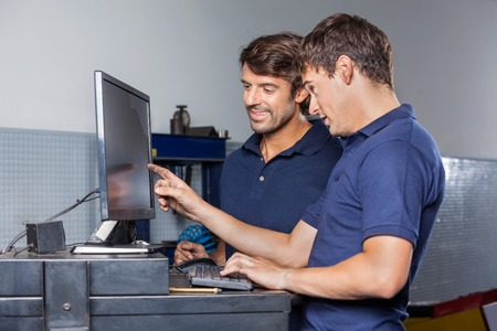 data entry: Male mechanics using computer together at counter in garage Stock Photo