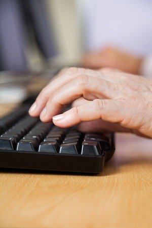 computer keyboard: Cropped hand of senior man using keyboard at desk in computer class Stock Photo