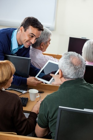 the elderly tutor: Senior male student asking question to teacher on digital tablet at desk in computer class