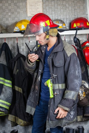 talkie: Young male firefighter using walkie talkie at fire station