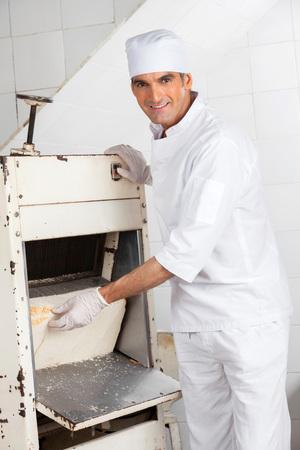 slicer: Portrait of smiling mature male baker using bread slicer at bakery