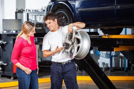 hubcap: Happy technician explaining metallic hubcap to female customer at garage