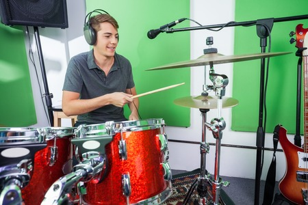 drummer: Smiling male drummer playing cymbal in recording studio Stock Photo