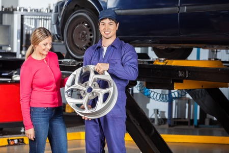 hubcap: Portrait of happy mechanic holding alloy with female customer examining it at garage