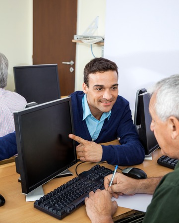 the elderly tutor: Happy male teacher showing something to senior student on computer at desk in classroom
