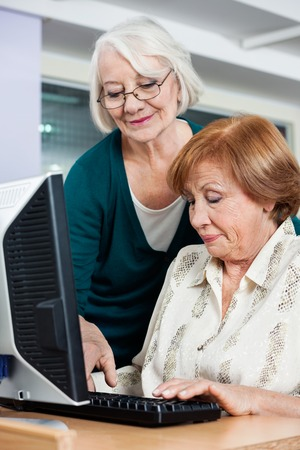 senior woman: Happy senior woman assisting female friend in using computer at classroom Stock Photo
