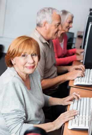 education help: Portrait of happy senior woman using computer at desk with classmates in classroom