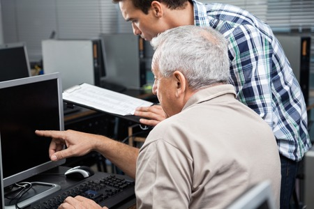 the elderly tutor: Male teacher holding clipboard while assisting senior man in using computer at classroom