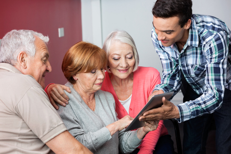 the elderly tutor: Male teacher assisting senior students in using digital tablet in classroom Stock Photo