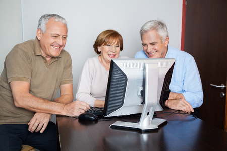 classmates: Happy senior woman with male classmates using computer at desk in classroom Stock Photo