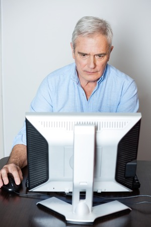usando computadora: Hombre mayor concentrada que usa el ordenador en el escritorio en la clase
