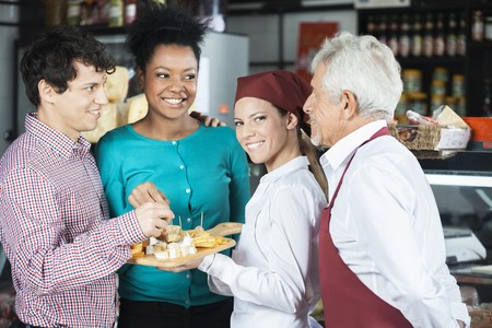 salespeople: Happy salespeople offering free cheese samples to customers in supermarket Stock Photo