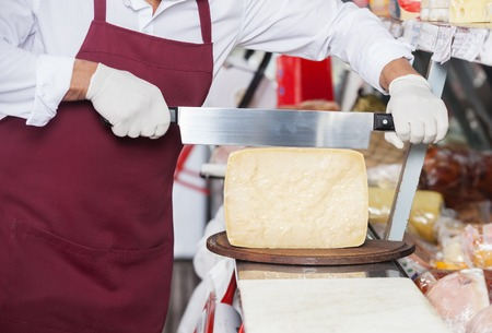 handled: Midsection of salesman slicing cheese with double handled knife at counter in shop