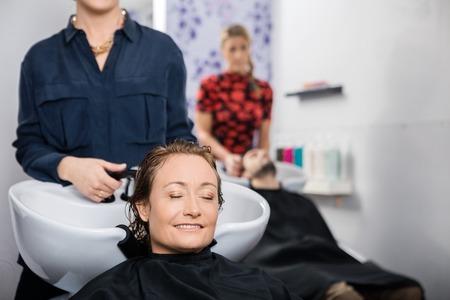 Relaxed Femme D Age Moyen Cheveux Obtenir Lave Par Coiffeur Dans Le
