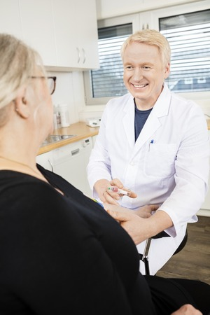 phlebotomist: Smiling mature male physician collecting senior patients blood for test in clinic