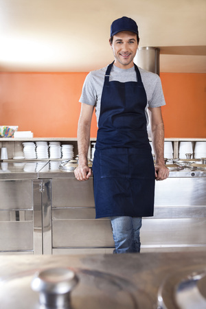 gelati: Portrait of confident waiter leaning on counter at ice cream parlor