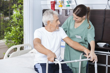 long term care services: Smiling senior man being helped by female nurse in using Zimmer frame at rehab center Stock Photo